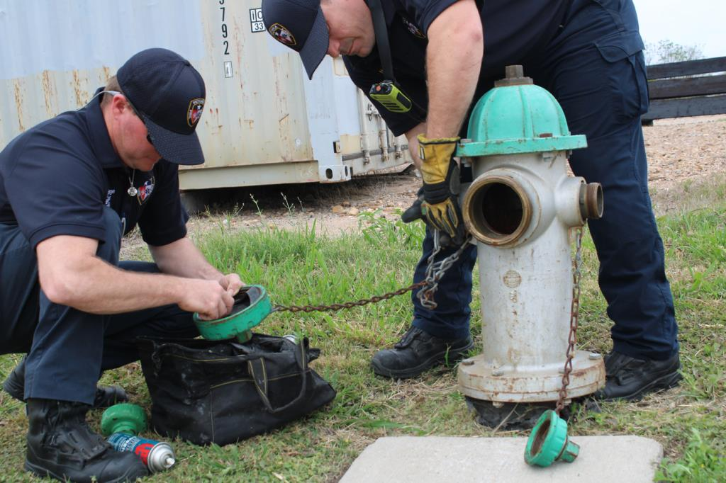 Fire department employees check fire hydrant