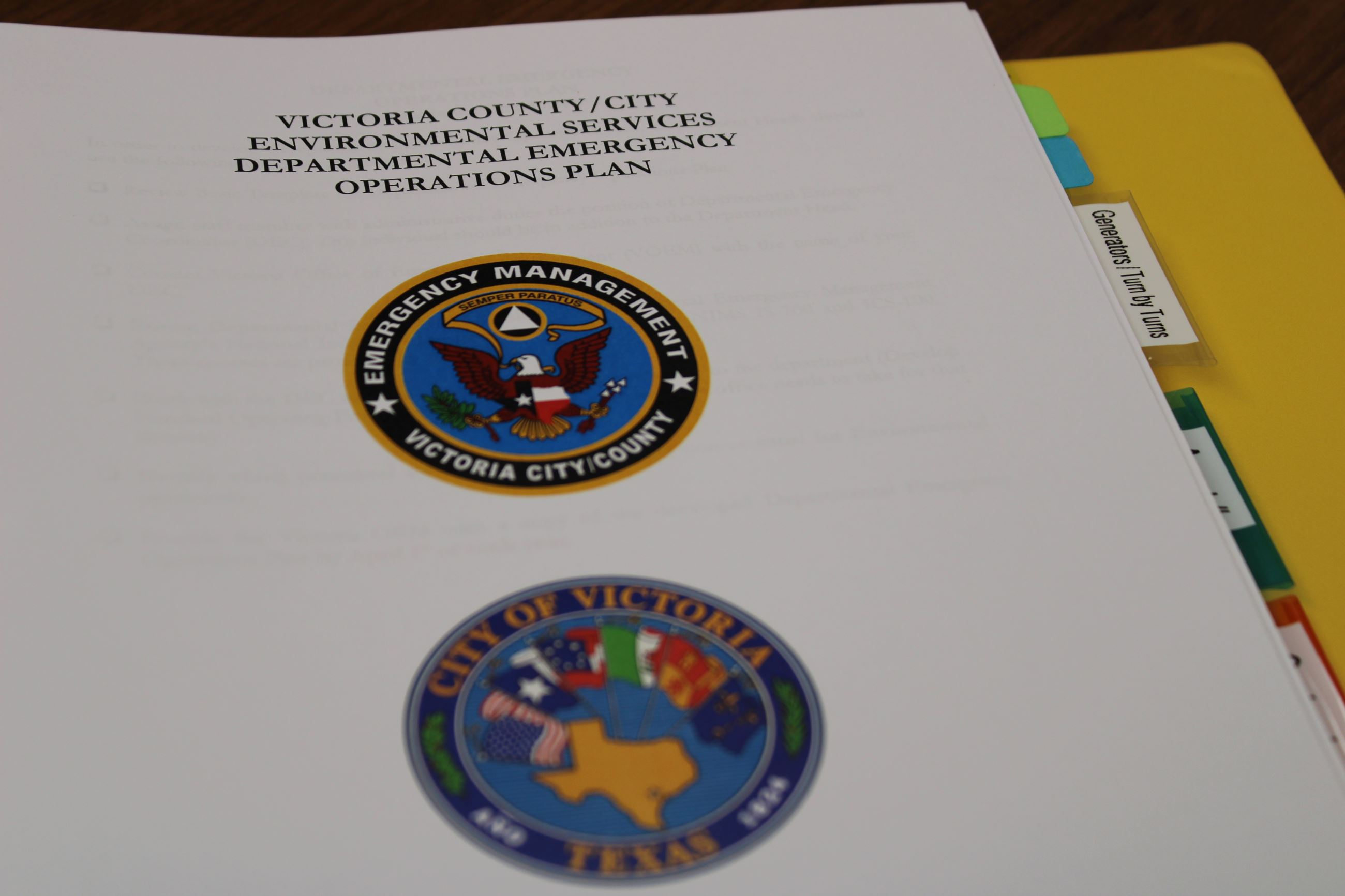 Yellow binder open to page displaying City and Office of Emergency Management logos