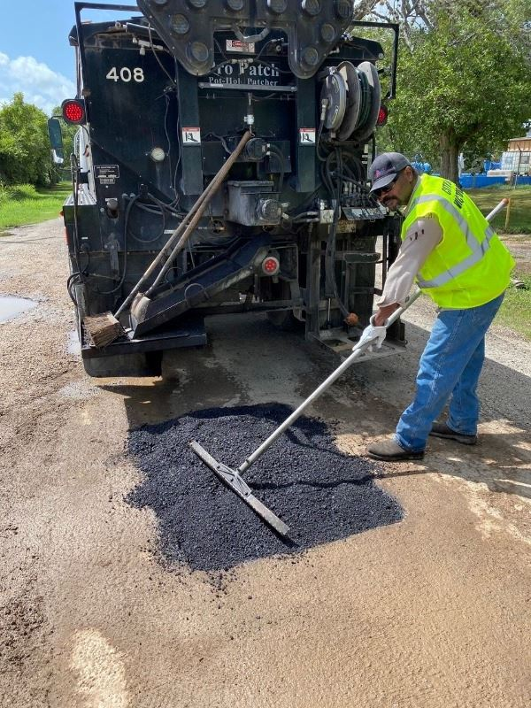 Bryant Stamps repairs a pothole using one of the City of Victoria's patch trucks.