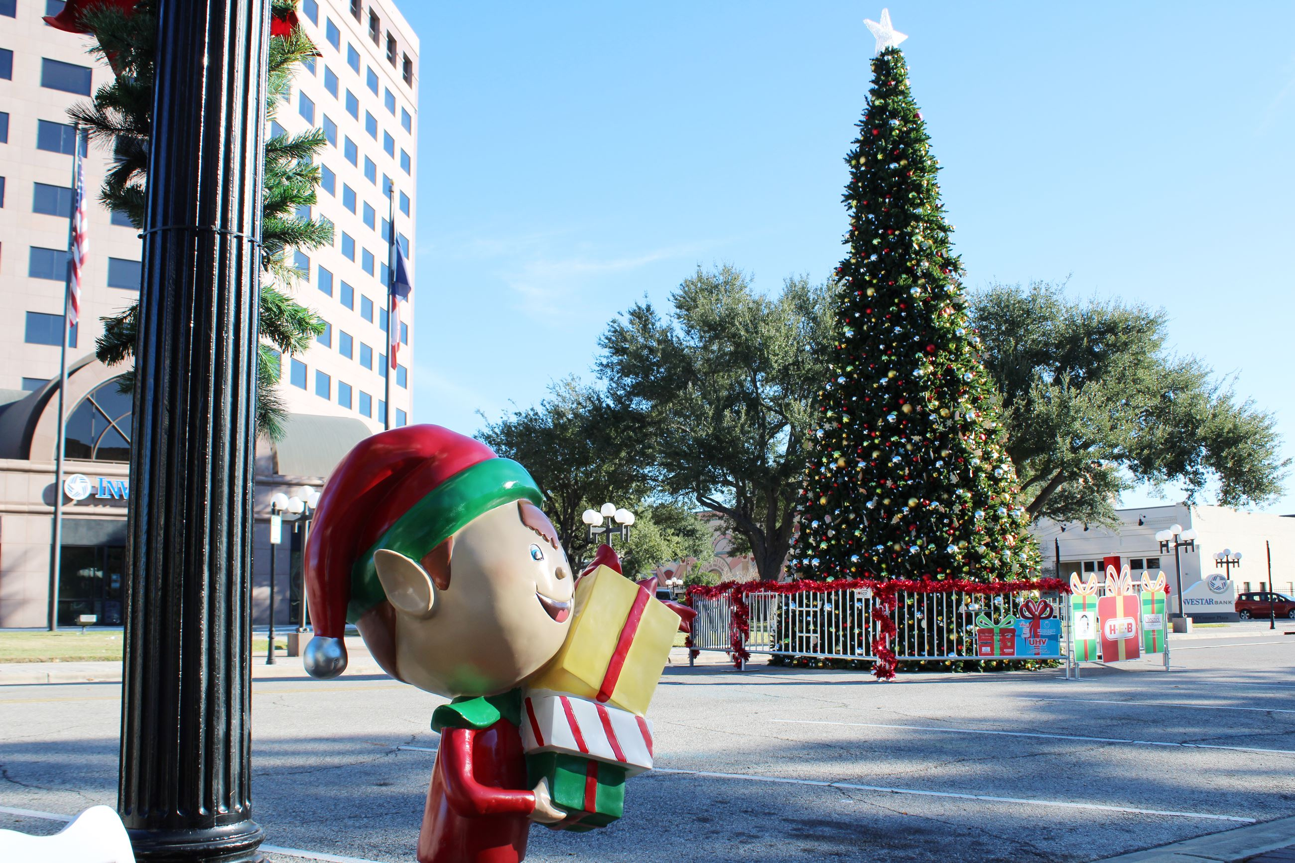 A plexiglass elf sculpture stands near a lamppost with the H-E-B Christmas Tree in the background.