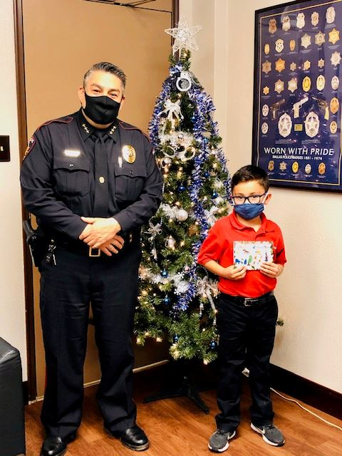 Policeman in uniform stands next to child holding card. Both stand in front of a Christmas tree.