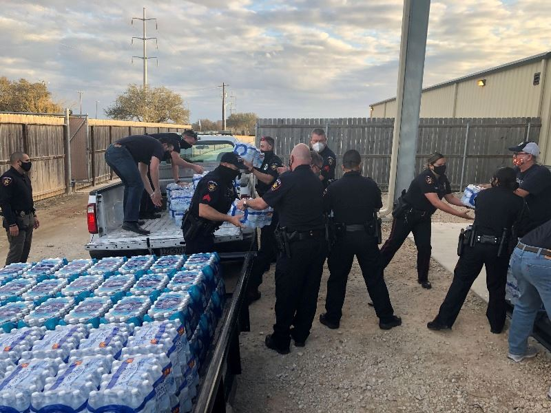 Workers load cases of bottled water onto a flatbed trailer
