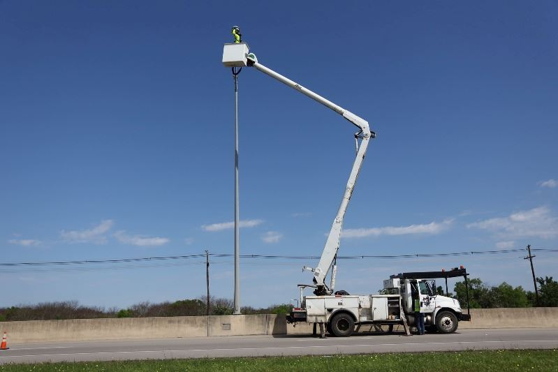 A cherry picker style truck extends its basket up to a street light on a highway.