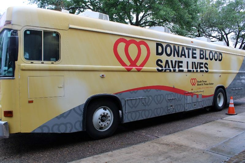Bus-style vehicle with the South Texas Blood and Tissue Center logo. Donate Blood, Save Lives.