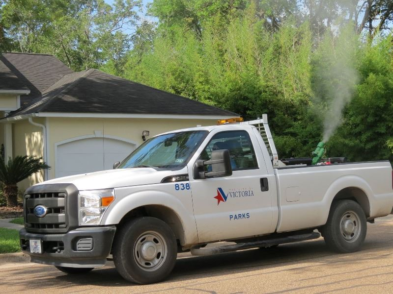 A truck with a Parks & Recreation logo sprays a white foggy pesticide in a neighborhood.