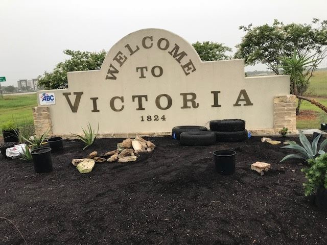 Welcome to Victoria sign with old tires in plant bed