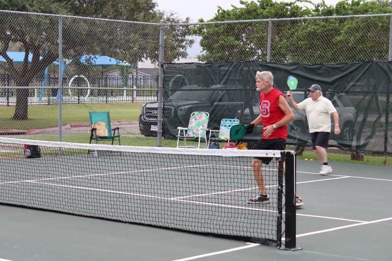 Two men stand on one side of the court during a game of pickleball.