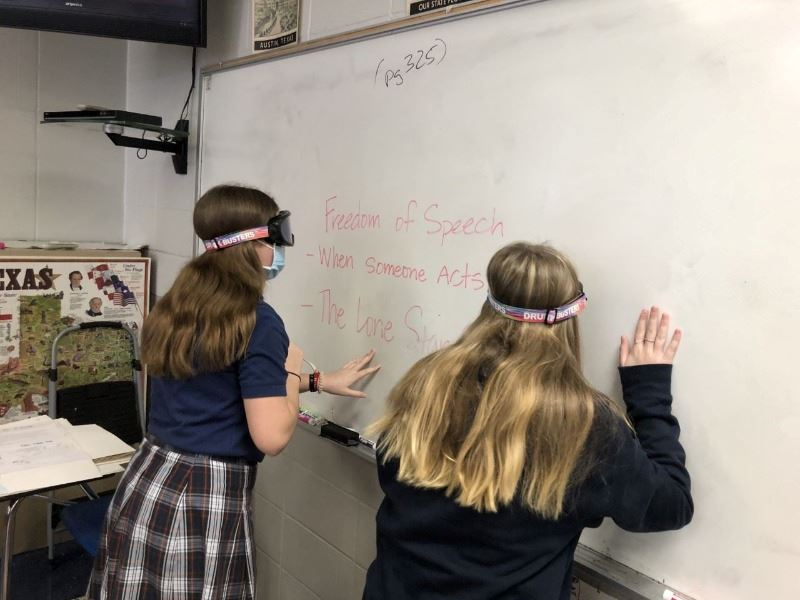 Two girls wearing impairment goggles stand close to a whiteboard with large lettering written on it.