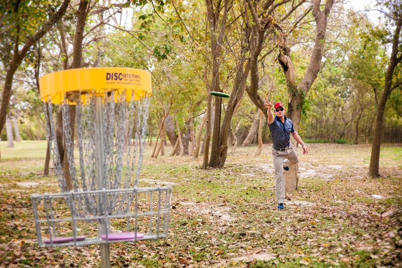 Man tosses disc golf disc into nearby basket at Riverside Park.