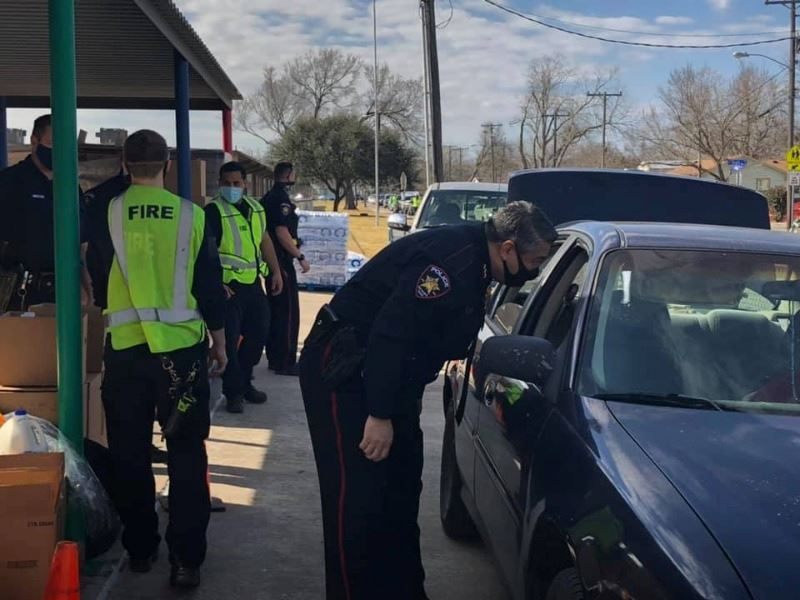 Workers in Police and Fire uniforms assist at a drive-thru event. Cars are lined up down the street.