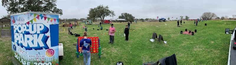 People of all ages play with giant Connect Four set, cornhole boards and other items in a wide field