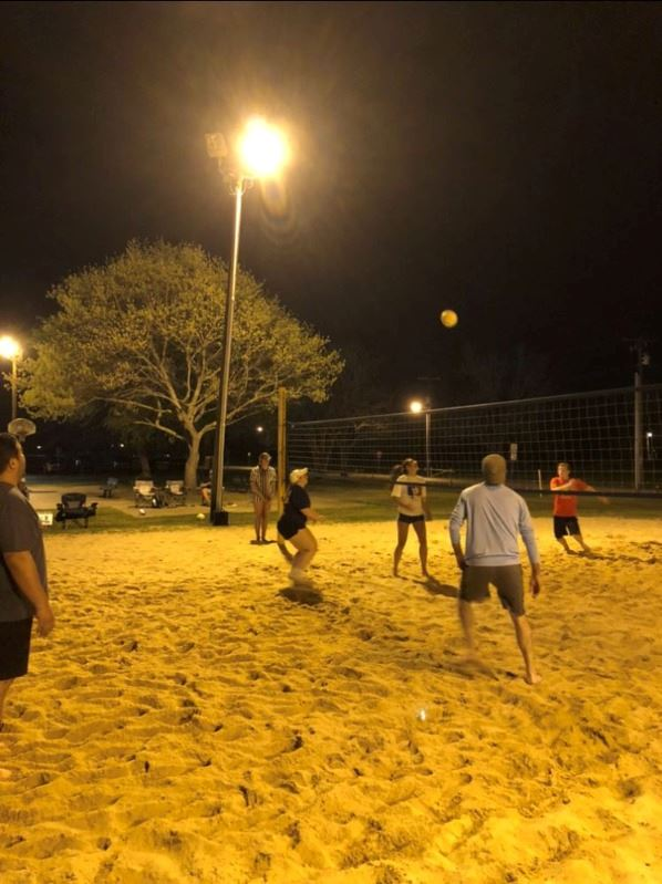 People play sand volleyball in the park at night under a street lamp.