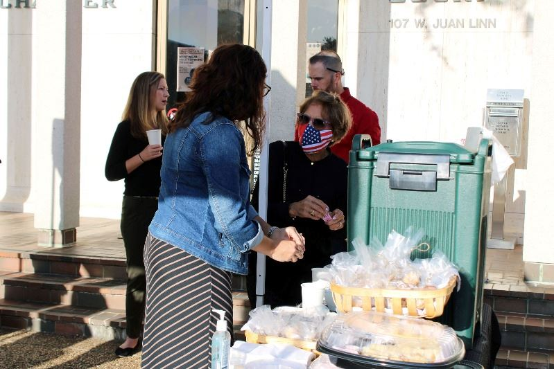 A few people stand near a refreshments table under a canopy in front of the Municipal Court building